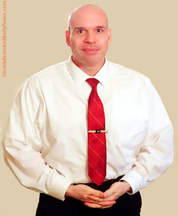 Picture of Mark Cammack wearing a long sleeve white dress shirt, red tie, and black pants. There is a grey background.